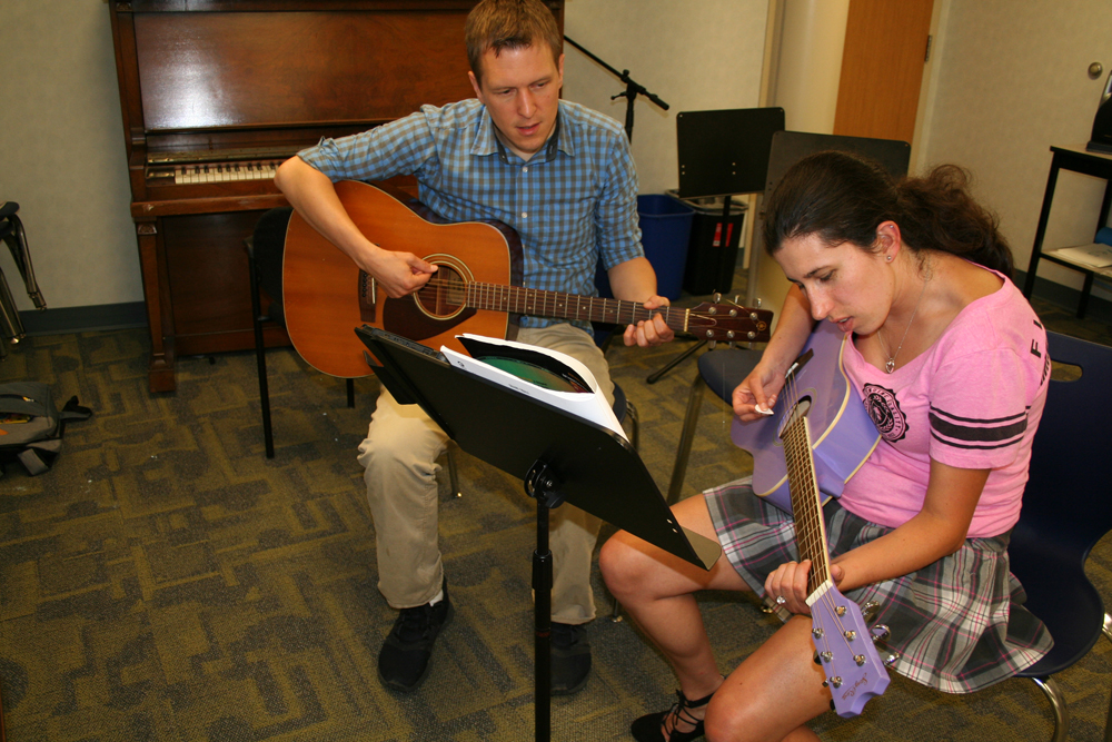 Teacher and student playing guitars