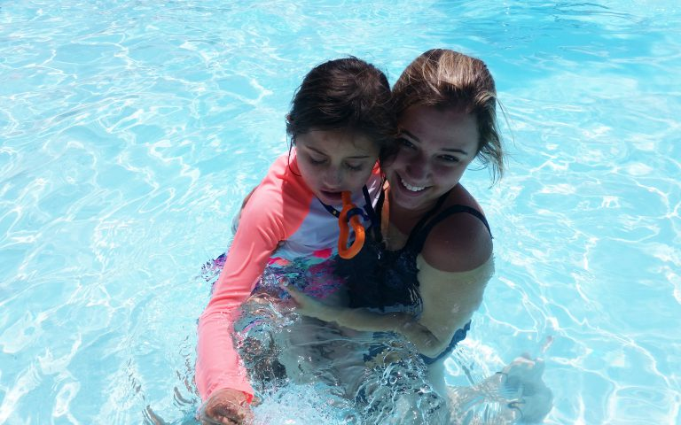 Swim instructor holding participant in swimming pool
